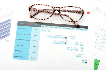Gantt diagram printed on white paper with glasses on it photo