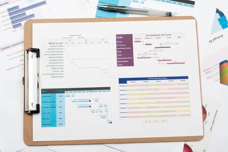 Gantt diagram printed on white paper with a pen on it