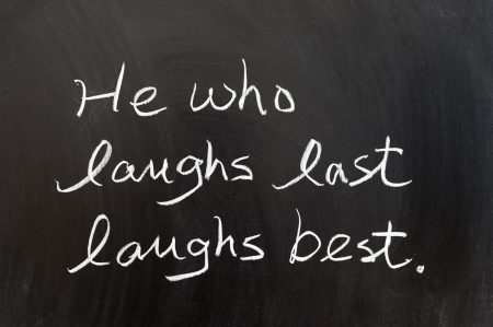 he laughs: He who laughs last laughs best saying written on chalkboard Stock Photo