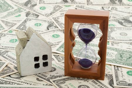 House model and hourglass on piles of paper money photo