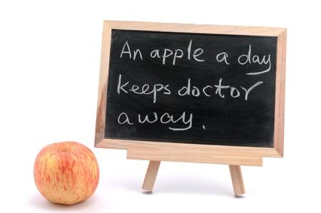 keeps: An apple a day keeps doctor away sayings written on blackboard Stock Photo