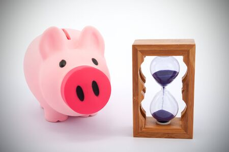 elapsed: Piggy bank and hourglass objects on white background