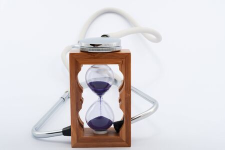 elapsed: Using stethoscope with hourglass on white background