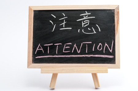 bilingual: Bilingual word of Attention in both Chinese and English written on blackboard over white background