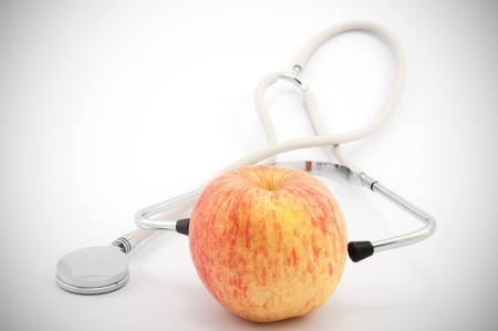 Using stethoscope to examine an apple on white background photo