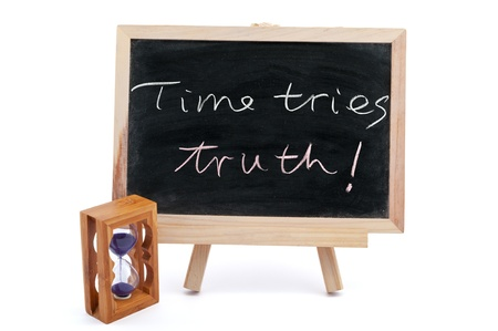 ordeal: Time tries truth sayiings written on chalkboard with an hourglass beside it