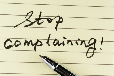 complaining: Stop complaining words written on lined paper with a pen on it Stock Photo