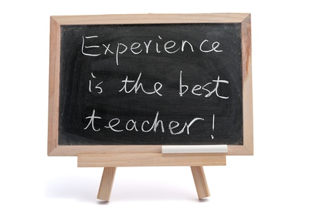 &quot,Experience is the best teacher&quot, saying written on blackboard over white background Stock Photo - 17071951