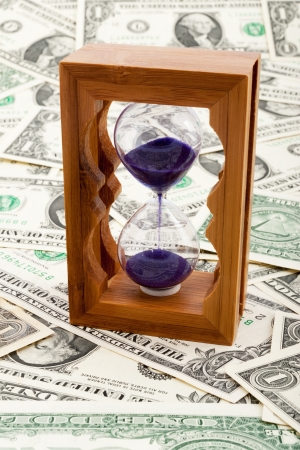 Hourglass on a layer of paper money photo