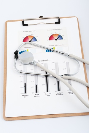 metrics: Business graph printed on the white paper with a stethoscope on it