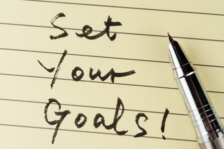 Set your goals words written on lined paper with a pen on it Stock Photo