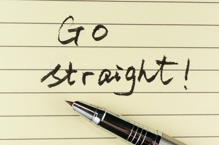 ruled: Go straight words written on lined paper with a pen on it