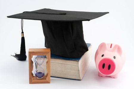 Graduation cap on a thick book with hourglass and piggy  bank photo