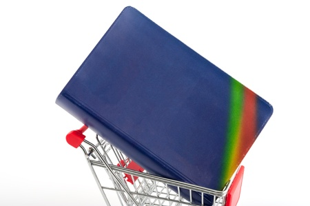 Book in a shopping cart isolated on white photo