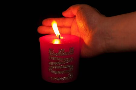 sheltering: Hand sheltering red candle from wind