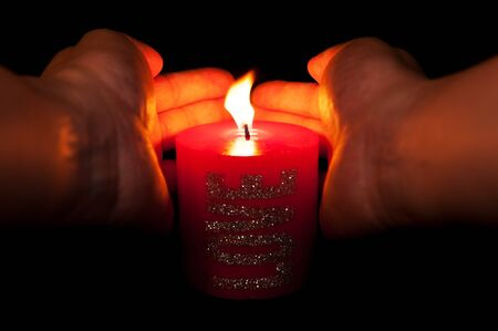 sheltering: Hands sheltering red candle from wind
