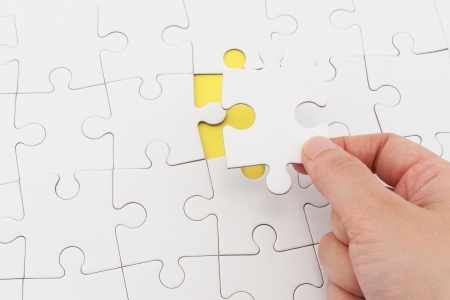 Hand holding puzzle piece and inserting it into group of white paper jigsaw puzzles Standard-Bild