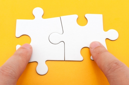 two piece: Hand holding two matching white paper jigsaw puzzles