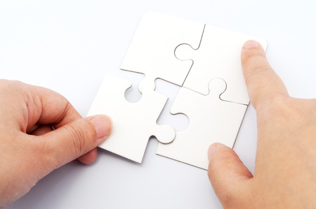 four hands: Hand holding puzzle piece and inserting it into group of white paper jigsaw puzzles Stock Photo