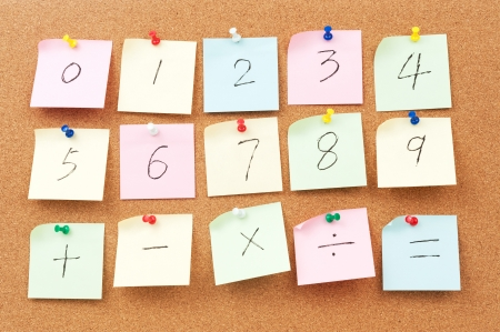 Numbers and Arithmetic operators written on paper and pinned on corkboard Stock Photo - 18656769