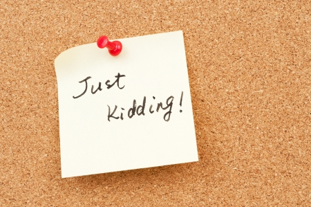 Just kidding words written on paper and pinned on corkboard Stock Photo - 18656692