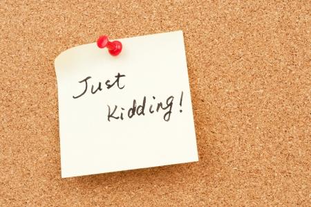 Just kidding words written on paper and pinned on corkboard Standard-Bild
