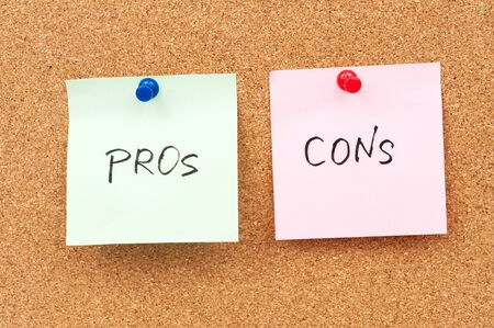 cons: Pros and cons written on paper and pinned on corkboard