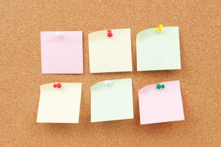 Group of thumbtack and note paper on corkboard photo