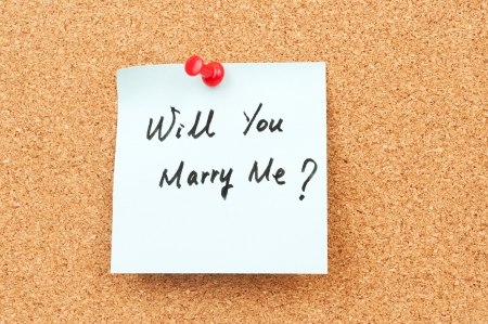 Will you marry me words written on paper and pinned on corkboard photo
