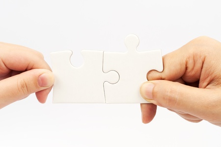 two pieces: Two hands holding puzzle pieces and connecting them