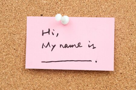 hello my name is: Note paper pinned on cork board which written Hi, My name is