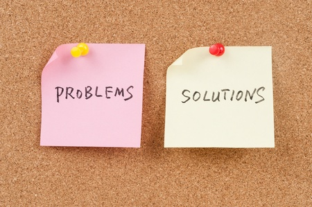 note board: Problems and solutions words written on paper and pinned on corkboard