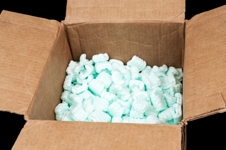 Cardboard box filled with styrofoam shipping peanuts isolated on black background photo