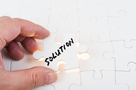 Hand holding puzzle piece which written solution word and inserting it into group of white paper jigsaw puzzles photo