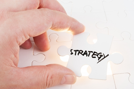 Hand holding puzzle piece which written strategy word and inserting it into group of white paper jigsaw puzzles photo