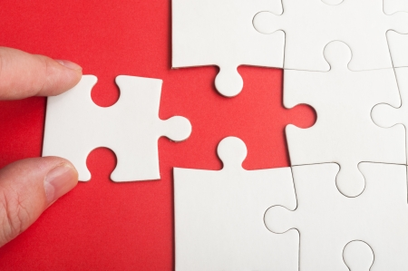 Hand holding puzzle piece and inserting it into group of white paper jigsaw puzzles photo