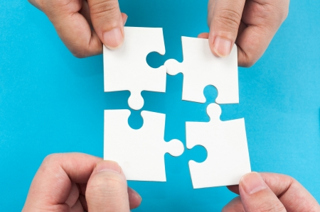 two pieces: Two hands holding jigsaw puzzle pieces and putting them together Stock Photo