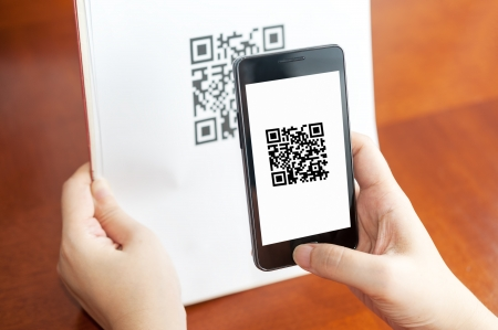 qr code: Hand holding a mobile and scanning QR code on the paper
