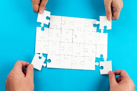 putting on: Two person holding jigsaw puzzle pieces and putting them together Stock Photo