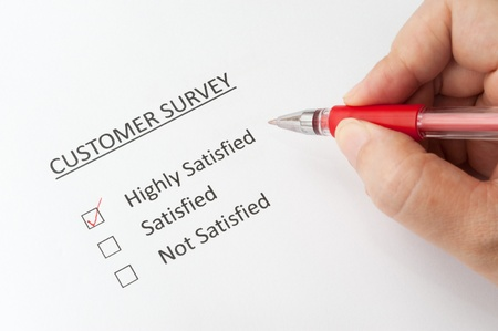 SATISFIED: Hand holding a pen and filling a  customer survey with options of highly satisfied, satisfied and not satisfied Stock Photo