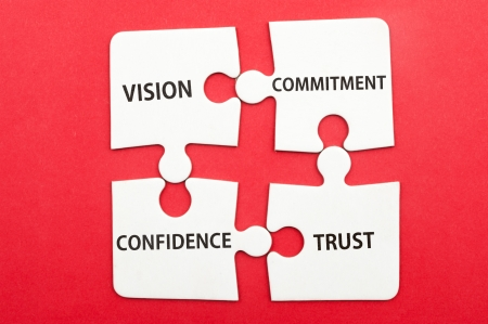 commitment: Business teamwork concept of vision, commitment, confidence, trust written on group of jigsaw puzzle pieces