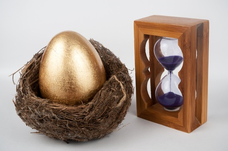 elapsed: A golden egg in the bird nest with hourglass beside