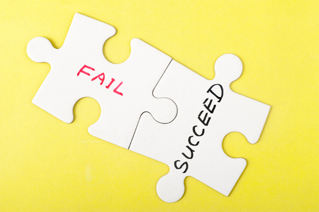 failed strategy: Fail or succeed words on two pieces of jigsaw puzzle