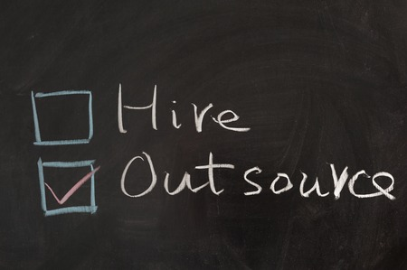 Choosing from hire and outsource concept words on blackboard