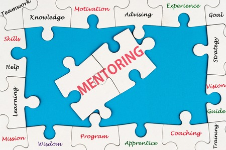 advising: Mentoring concept word cloud on group of jigsaw puzzle pieces