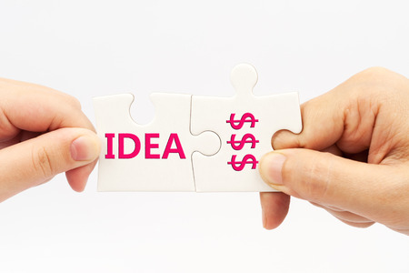 Two hands holding puzzle pieces which written Idea and money words photo