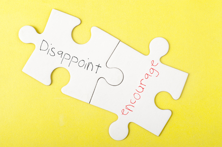 disappoint: Disappoint and Encourage words written on two pieces of jigsaw puzzle