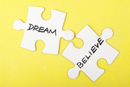 beliefs: Dream or believe words on two pieces of jigsaw puzzle Stock Photo
