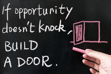 If opportunity doesn't knock, build a door words written on blackboard using chalk Banco de Imagens