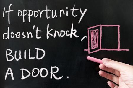 If opportunity doesn't knock, build a door words written on blackboard using chalk Archivio Fotografico